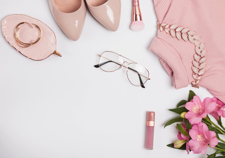 Stylish pale pink feminine accessories on the white background.