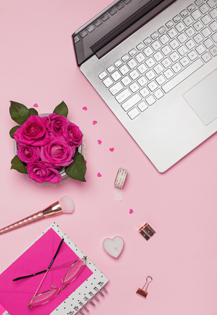 Laptop, roses, small papr hearts and other accessories on the pink background, top view