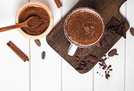 Heiße Schokolade in der Tasse, Kakaobohnen und Pulver auf dem weißen Holztisch Standard-Bild