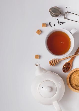 Composition créative de l'heure du thé. Tasse, théière et sucre sur fond blanc, vue de dessus