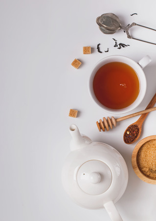 Tea time creative composition. Cup, teapot and sugar on the white background, top view