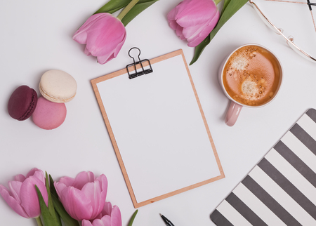 Feminine styled work place with tulips and coffee. Фото со стока