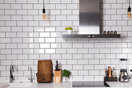 Modern kitchen with brick white tile wall and differet utensils Banco de Imagens