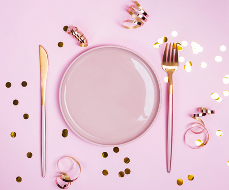 Pink plate, fork and knife and golden connfetti and ribbons on pink background, Фото со стока - 120847898