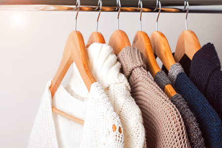 Knitted sweaters on hangers on the white wall background