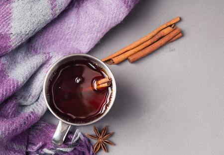 Hot tea or mulled wine in stainless steel cup and checkered plaid on the grey background