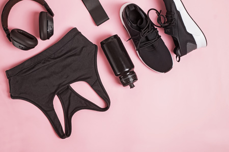 Black color fitness accessories set on pink background. Imagens