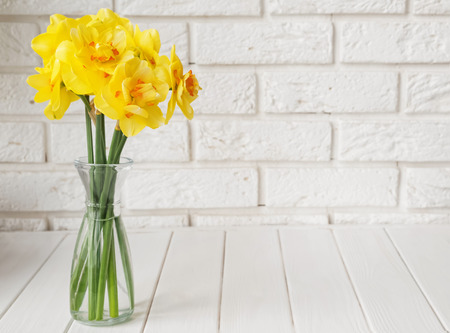 Bouquet of beautiful spring flowers over the white brick wall