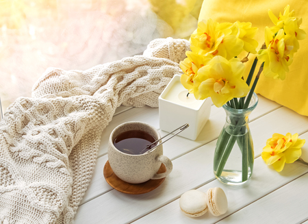 Spring still life with yellow flowers, tea and candle, Foto de archivo