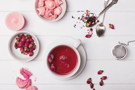 Floral tea in a cup, dried roses and other tea accessories on the white background