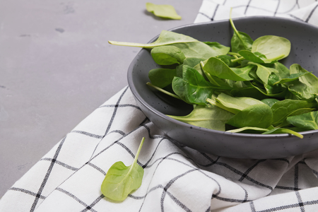 Baby spinach leaves in a rustic bowl on the gray stone background