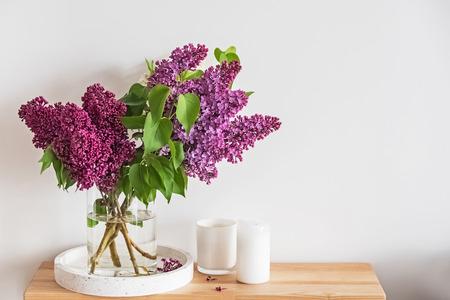 Ramo de hermosas flores lilas de pie en un jarrón de vidrio en el pequeño soporte de madera