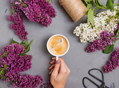 Womans hand holding a Cup of coffee on the table with beautiful lilac flowers,
