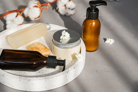 Creams, shampoo and other hair and body care on the grey stone background with natural sunlight