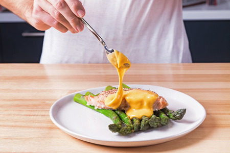 Mans hands pouring hollandaise sauce on top of delicious baked salmon with steamed green asparagus