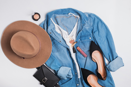 Modern stylish feminine outfit with denim shirt, suede flat shoes and hat