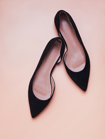 Feminine black suede shoese isolated on peach color background