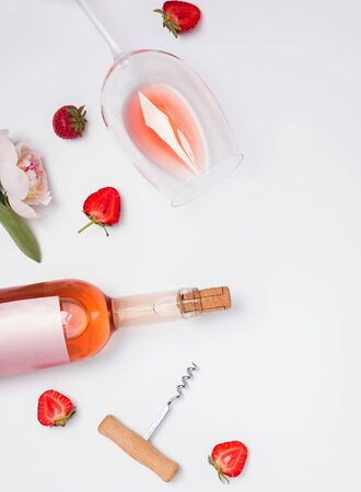 Creative summer flat lay with rose wine, delicious strawberries and beautiful peonies on the white background