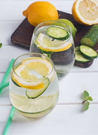 Water infused with mint, lemon and cucucmber on the white wooden table