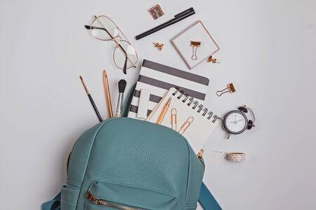 Studentenrucksack mit verschiedenen Schreibwaren und Lernmaterialien auf weißem Hintergrund, Draufsicht. Zurück zum Schulkonzept. Standard-Bild