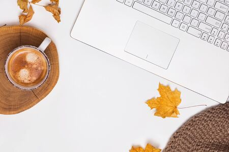 Autumn workplace concept with coffee and yellow leaves