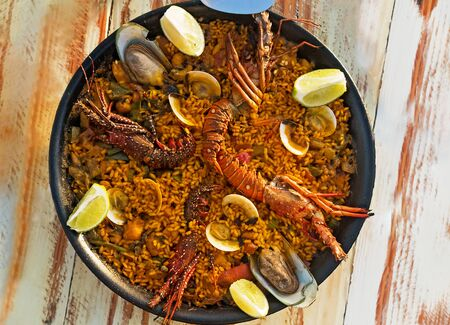 Delicious seafood paella with shrimps and clams, on the wooden table