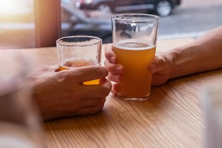 Two mans hands holding beer glasses or clinking in the pub Stockfoto