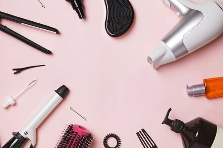 Hair styling and care items and products on pink background Фото со стока
