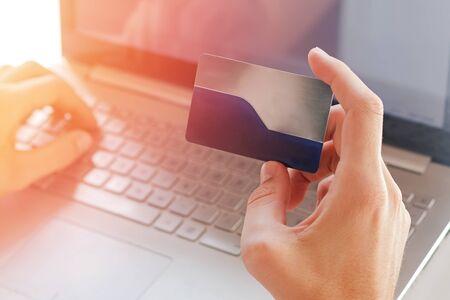 Man holding a plastic credit card near the computer close-up. Фото со стока