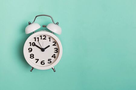 Vintage alarm clock isolated on pastel mint background,