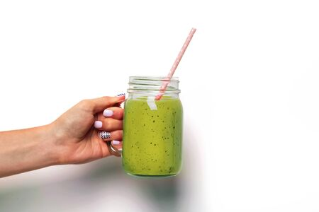 Womans hand holding a glass jar with green smoothie