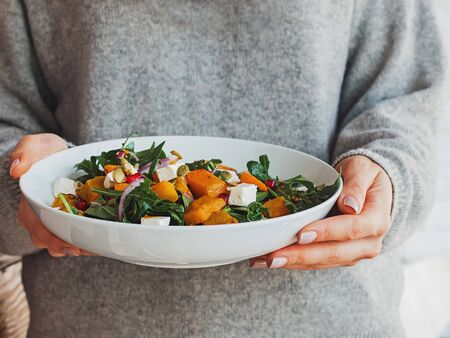 Woman holding a bowl of salad with pumpkin, arugula, feta cheese and pomegranate seeds. Фото со стока