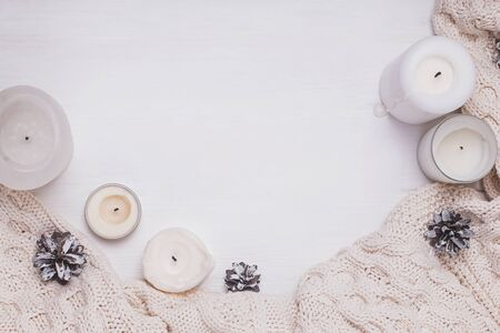 Creative winter composition with candles, pine cones and knitted sweater