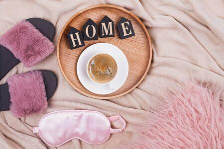 Creative composition with coffee, slippers, slipping mask and wooden letters arranged into a word Home