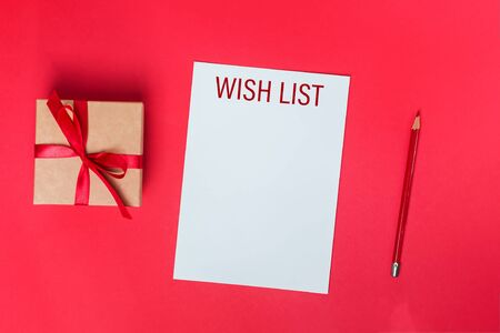 Blank paper with caption wishlist, giftbox and red pencil on red background, top view. Stock Photo
