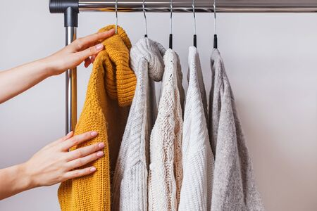 Womans hands choosing yellow knitted sweater among others on hanger