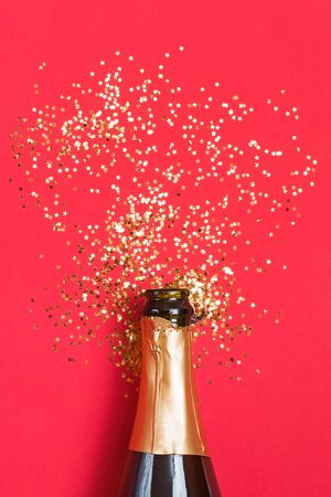 Champagne bottle with golden star shaped confetti on red background. Stock Photo