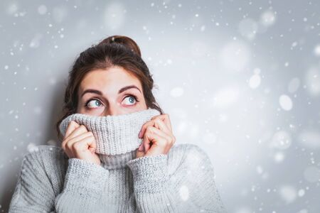 Happy young woman in warm cozy sweater dreaming, looking to the top.