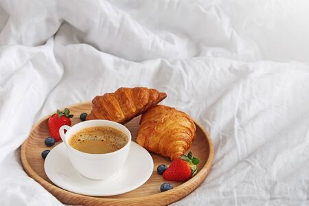 Coffee and croissants on the white bedsheets close-up