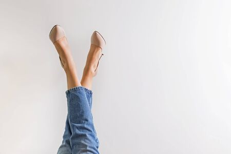 Female legs dressed in jeans and high heel shoes