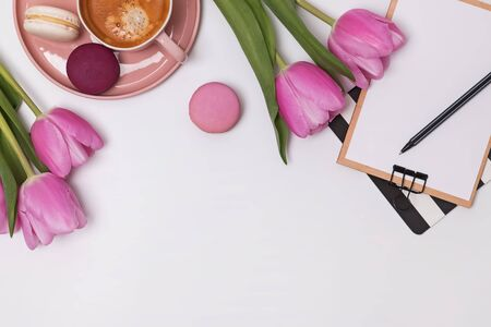 Beautiful pink tulips, cup of coffee and macarons on the white table Standard-Bild - 134852503
