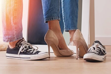 Woman choosing between two pairs of shoes high heels and flat sneakers. 스톡 콘텐츠