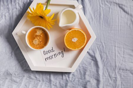 Tray with coffee, milk, orange and yellow flower on it standing on the bed Standard-Bild - 134852222