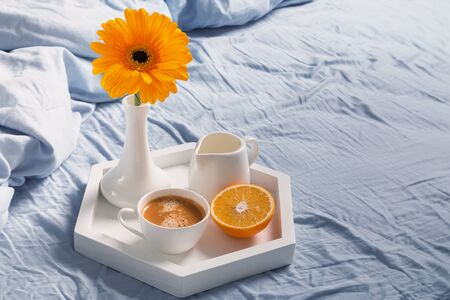 Tray with coffee, milk, orange and yellow flower in a vase on it standing on the bed. Stock Photo