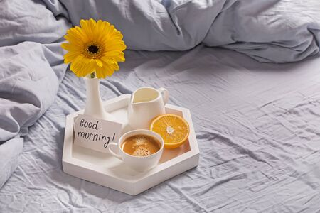 Tray with coffee, milk, orange, yellow flower in a vase and card with text Good morning Standard-Bild - 134852224