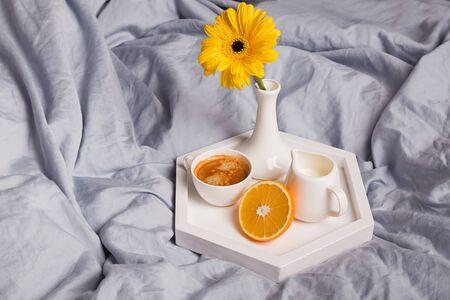 Coffee, half of orange, milk and gerbara flower in a vase standing on the bed. Standard-Bild - 134852225
