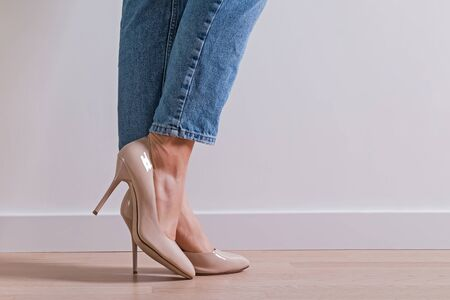 Womans feet wearing high heel shoes and jeans standing on the wooden floor close-up Stock Photo