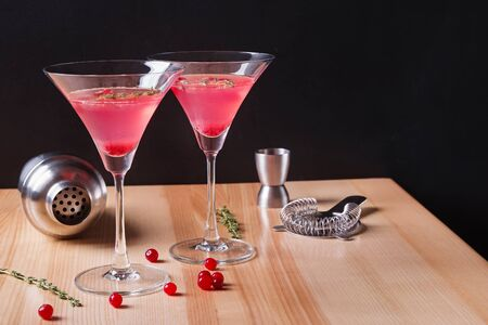 Two martini glasses filled with red color cranberry cocktail and barmen tools
