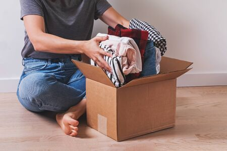 Unrecognizable woman putting clothes in cardboard box while sitting on the floor. Donation or packing for moving stuff in new place.