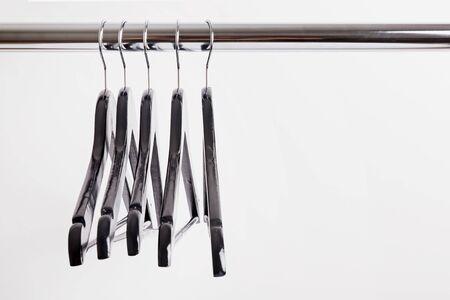 Empty black hangers on a rail close-up.